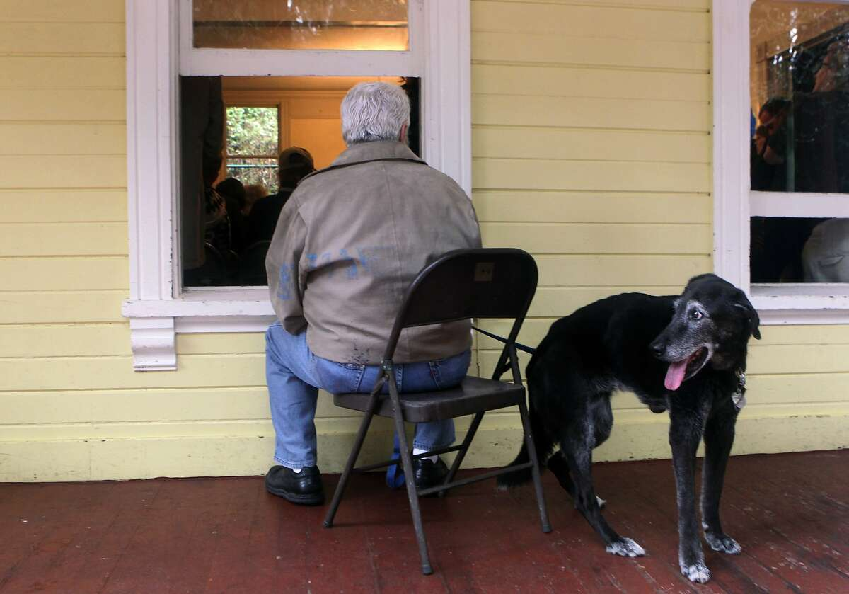 David Hurowitz and his dog Guinness listen from the porch of the Trocadero Clubhouse where a standing-room-only crowd attended a public meeting at Stern Grove in San Francisco, Calif. on Thursday, Jan. 30, 2014, to discuss the GGNRA's proposed rules and restrictions on off-leash dogs.