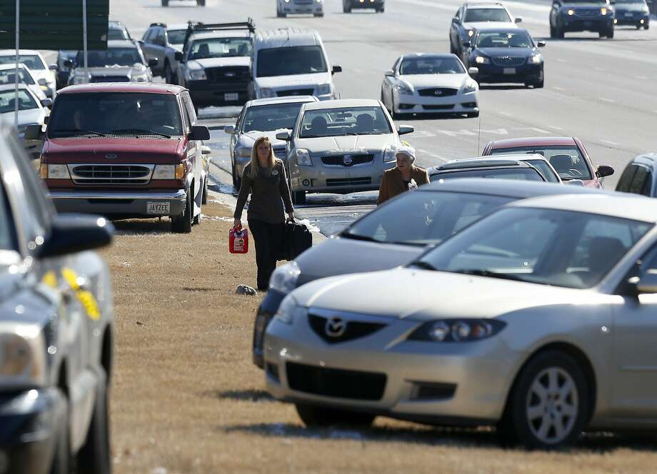 Karen Hurst (left) carries a gas can as she helps Ann Batsun recover her car, one of thousands abandoned on Georgia's highways during the winter storm. Photo: John Bazemore, Associated Press
