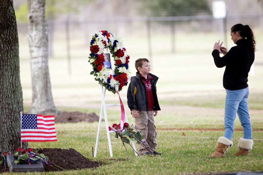 Former NASA employee Sandra Hammack takes a photo of her son Buzz Bain, 4, by the memorial wreath of the Apollo 1 crew during the Day of Remembrance, Thursday, Jan. 30, 2014, in Houston. Photo: Marie D. De Jesus, Houston Chronicle / © 2014 Houston Chronicle