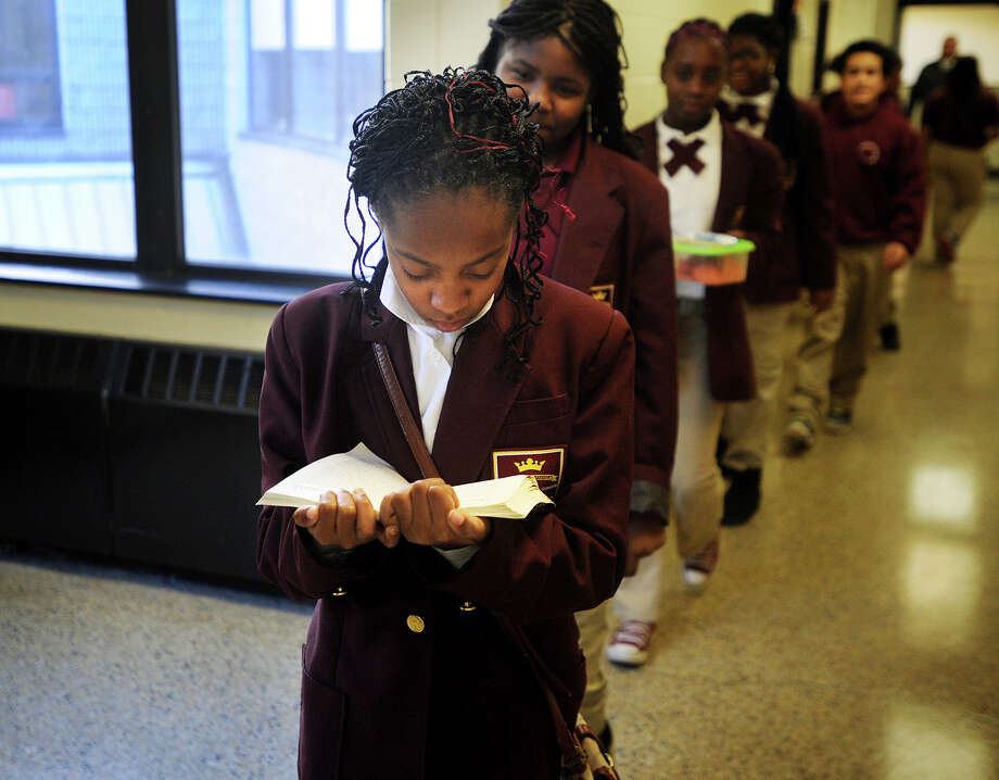 Nataya Vinson, 11, reads a book as she walks quietly single file with her 6th grade classmates to lunch at Dunbar School in Bridgeport, Conn. on Thursday, January 30, 2014. Photo: Brian A. Pounds / Connecticut Post