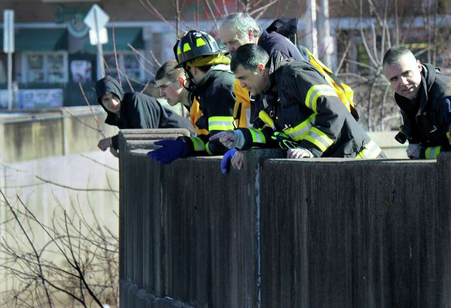 Emergency personnel peer over the wall surrounding the Still River near Crosby Street Thursday morning, January 30, 2014, in Danbury, Conn. after responding to reports of a person falling into the icy river. Authorities said no one was found and the report appeared to be unsubstantiated. Photo: Carol Kaliff / The News-Times