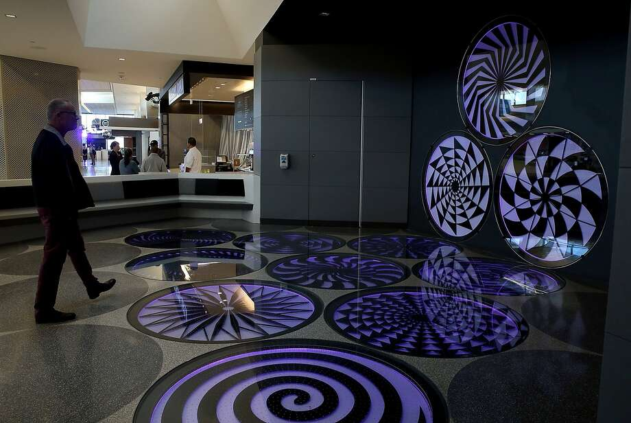 "Artist Eric Staller walks past his art installation ""Spirogyrate"" inside SFO's United Airlines terminal. Photo: Justin Sullivan, Getty Images"