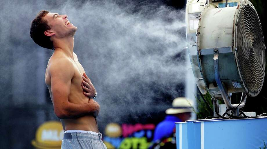 Poland's Jerry Janowicz is sprayed with cool water at the Australian Open tennis championship in Melbourne earlier this month. When the temperature topped 109 degrees, play was halted. Photo: Fiona Hamilton / Associated Press / Tennis Australia