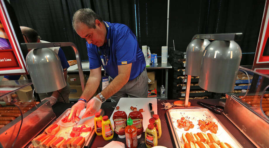 Jim Powers arranges tequila lime flavored sausages for CST Brands Inc. convenience store managers  to taste test new products. One of our readers questions the wisdom of running such a story on the front page. Photo: Jerry Lara / San Antonio Express-News / © 2014 San Antonio Express-News
