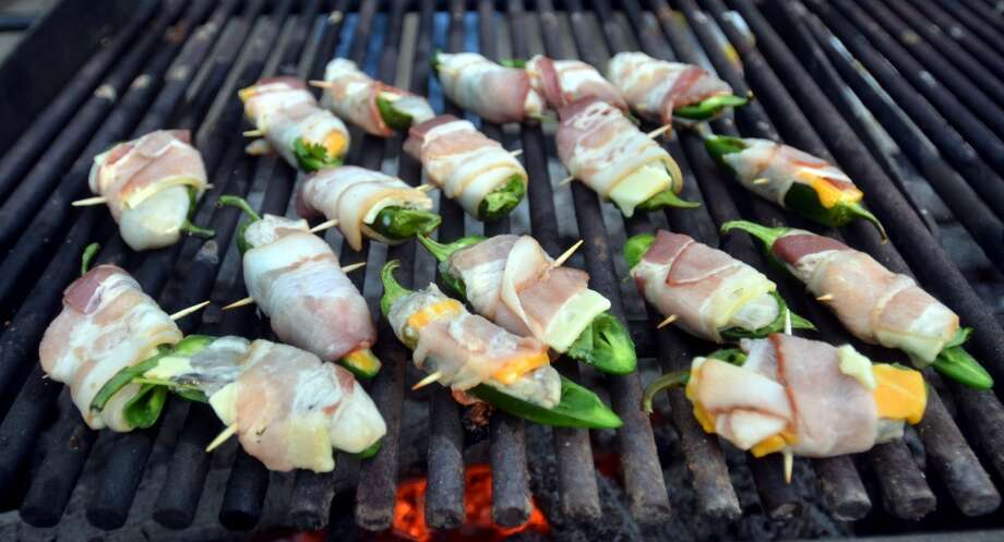Local garden jalapenos stuffed with cheese and wrapped in bacon cook on the grill at Slow Food Beaumont's Oysterfest at Village Creek State Park in Lumberton on Jan. 25, 2013. Photo: Cat5