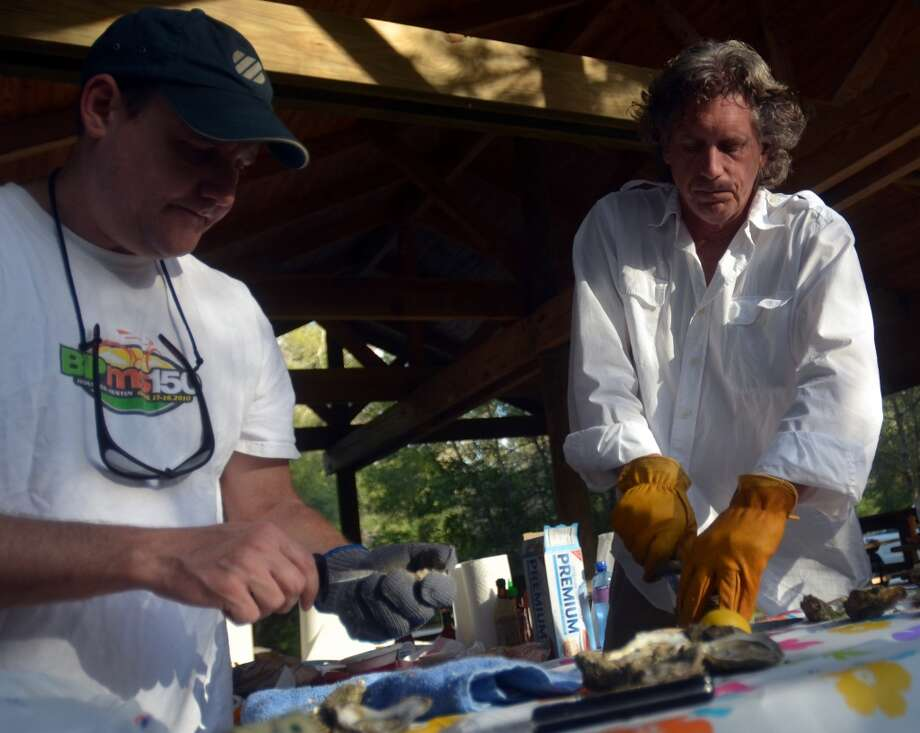 Chris Boone, left, and Eric Bender, right, shuck oysters during Slow Food Beaumont's Oysterfest at Village Creek State Park in Lumberton on Jan. 25, 2013. Photo: Cat5
