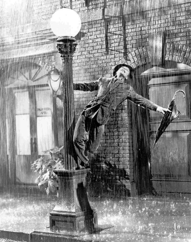 "FILE - In this undated file photo, Gene Kelly performs in the 1952 film ""Singin' in the Rain."" The grey wool suit Kelly wore in the movie is going up for auction after being kept in a closet by a memorabilia collector for more than four decades. (AP Photo/File) Photo: Anonymous, Associated Press"