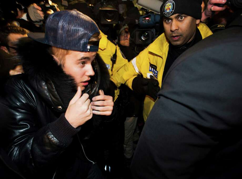 Canadian musician Justin Bieber is swarmed by media and police officers as he turns himself in to city police for an expected assault charge, in Toronto, on Wednesday, Jan. 29, 2014. A police official said the charge has to do with an alleged assault on a limo driver in December. (AP Photo/The Canadian Press, Nathan Denette) ORG XMIT: NSD101 Photo: Nathan Denette / CP