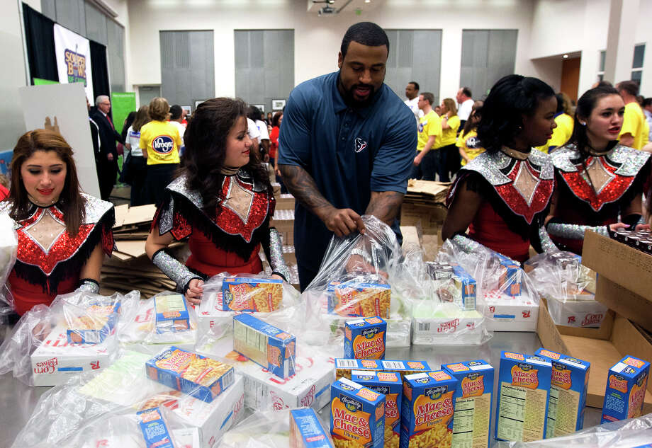 Houston Texans offensive tackle Duane Brown helps package donated goods during the kickoff of the Souper Bowl of Caring Houston 2014 at the Houston Food Bank, Wednesday, Jan. 15, 2014, in Houston. The Houston campaign is the largest one in the nation, with a 2014 goal of generating enough food and money to provide 2.8 million meals to hungry neighbors in Houston. The campaign is a nationwide, grassroots movement of caring utilizing the energy of the Super Bowl to mobilize youth to fight hunger and poverty in their local communities. (Cody Duty / Houston Chronicle) Photo: Cody Duty, Staff / © 2014 Houston Chronicle