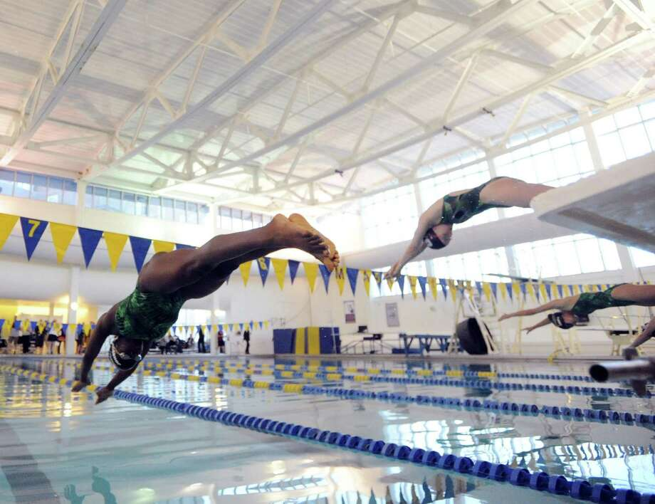 At left, Shaun Johnson of Convent of the Sacred Heart, goes off the block at the start of the 50 freestyle race during the high school swim meet between Convent of the Sacred Heart and Greenwich Academy at the YMCA of Greenwich, Wednesday, Jan. 29, 2014. Photo: Bob Luckey / Greenwich Time
