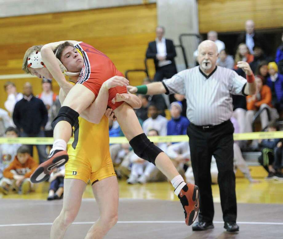 Brunswick's Jimmy Bell (light yellow outfit) goes up against Alex Jarombek (dark red outfit) of Greenwich in the 132 pound weight class match that Bell won during high school wrestling match between Greenwich High School and Brunswick School at Brunswick in Greenwich, Tuesday, Jan. 28, 2014. Photo: Bob Luckey / Greenwich Time