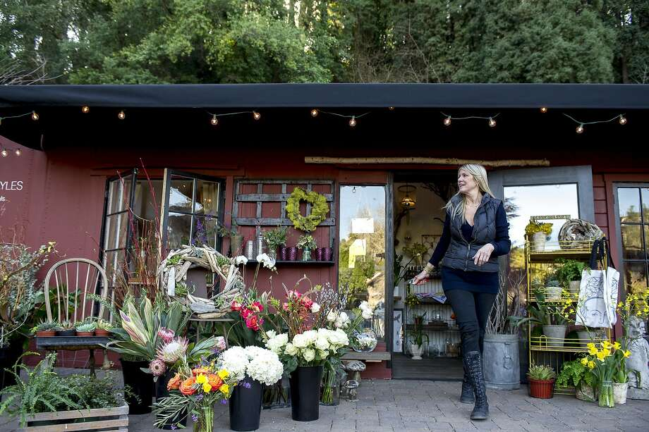 Floral designer Gayle Nicoletti has opened a Bloomingayles store in the recently renovated Mill Valley Lumber Yard, above. Below, Nicoletti combines hellebore and sage in a mason jar arrangement. Photo: Dan Evans