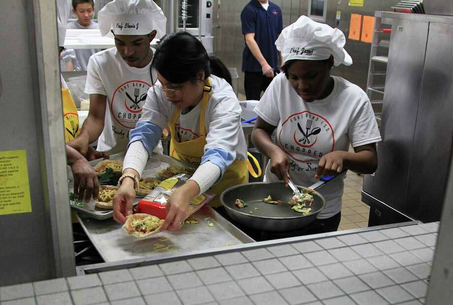"Maria Gomez, of Colony Bend Elementary School is assisted by Culinary Arts students Steven Jackson, left, and Jasminue Matthews at Dulles High School Cafeteria, during the second annual cooking competition based loosely on the Food Network's hit show, ""Chopped"", Thursday, Jan. 30, 2014. Photo: Karen Warren, Houston Chronicle / © 2013 Houston Chronicle"