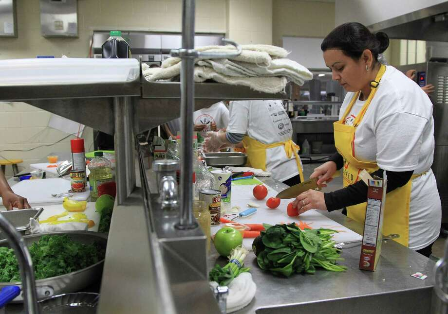 "Annie Hernandez cuts up ingredients at Dulles High School Cafeteria, during the second annual cooking competition based loosely on the Food Network's hit show, ""Chopped"", Thursday, Jan. 30, 2014. Photo: Karen Warren, Houston Chronicle / © 2013 Houston Chronicle"