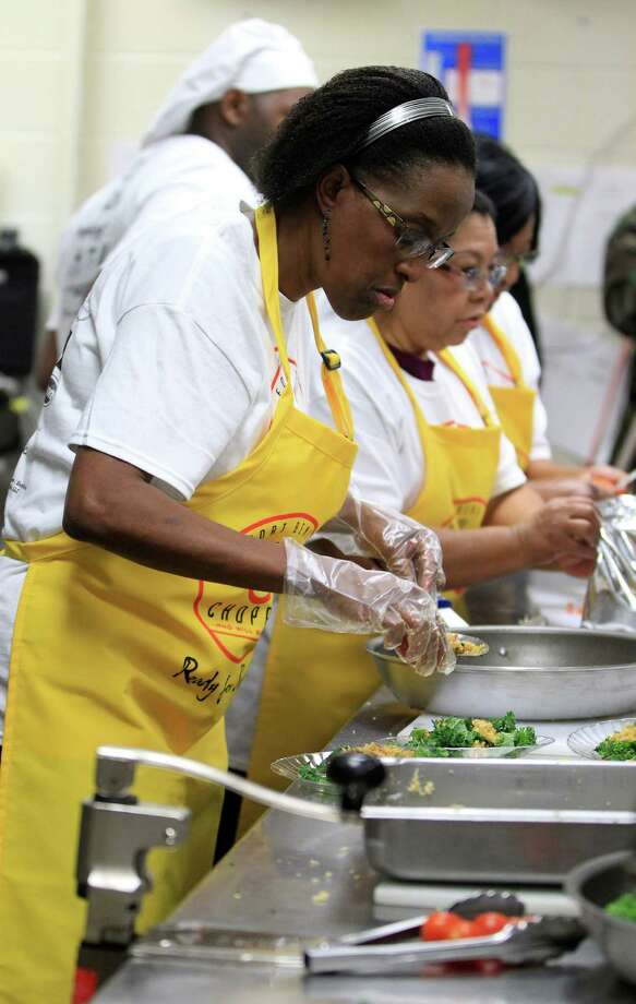 "Danita Brown of Oyster Creek Elementary cooks at Dulles High School Cafeteria, during the second annual cooking competition based loosely on the Food Network's hit show, ""Chopped"", Thursday, Jan. 30, 2014. Photo: Karen Warren, Houston Chronicle / © 2013 Houston Chronicle"
