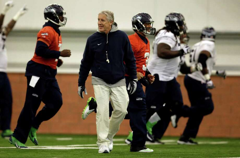 Seattle Seahawks head coach Pete Carroll watches as members of his team warms up during NFL football practice Thursday, Jan. 30, 2014, in East Rutherford, N.J. The Seahawks and the Denver Broncos are scheduled to play in the Super Bowl XLVIII football game Sunday, Feb. 2, 2014. (AP Photo) ORG XMIT: NJJR119 Photo: Byline Withheld / AP