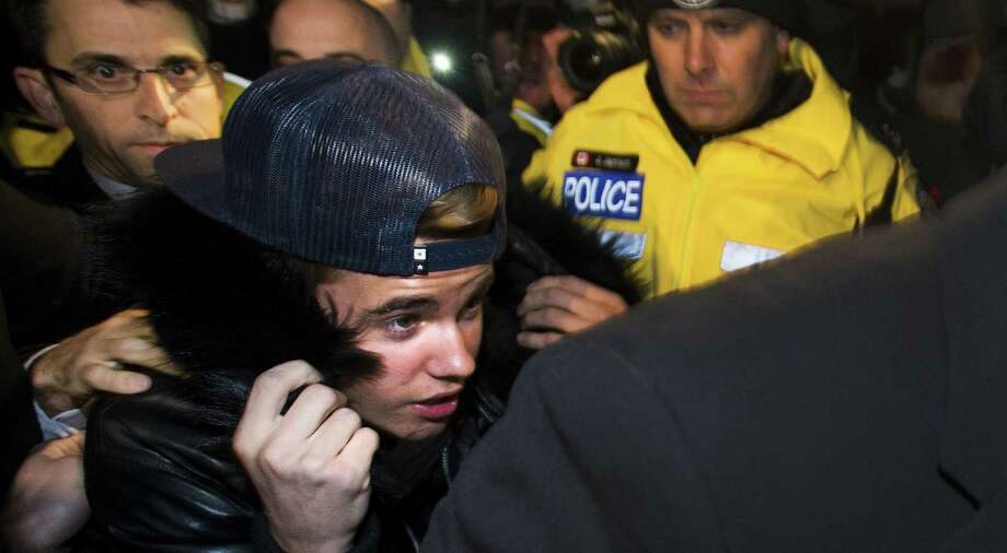 Canadian musician Justin Bieber is swarmed by media and police officers as he turns himself in in Toronto. Photo: Nathan Denette / Canadian Press / CP