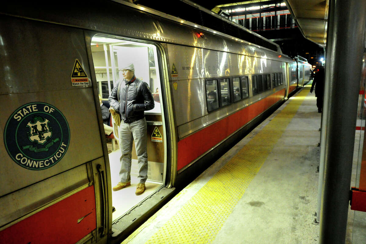 A commuter stands while riding a Metro-North train towards New Haven during rush hour at the Stamford, Conn., station on Thursday, Jan. 30, 2014.