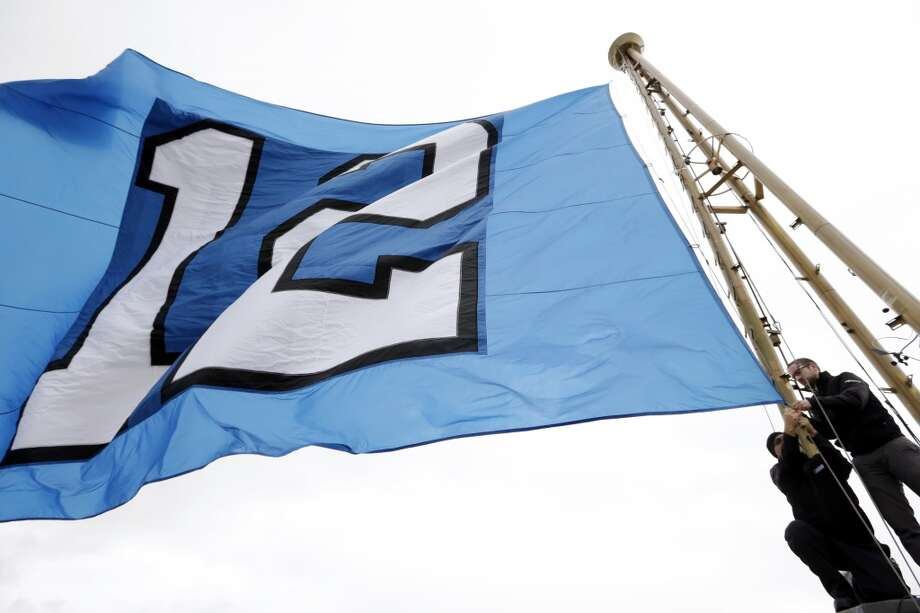 "Workers re-set the ""12th Man"" flag, honoring Seattle Seahawks fans, after it was raised atop the Space Needle Wednesday, Jan. 29, 2014, in Seattle. The Seahawks play the Denver Broncos in Super Bowl XLVIII on Sunday. (AP Photo/Elaine Thompson) Photo: Elaine Thompson, Associated Press"