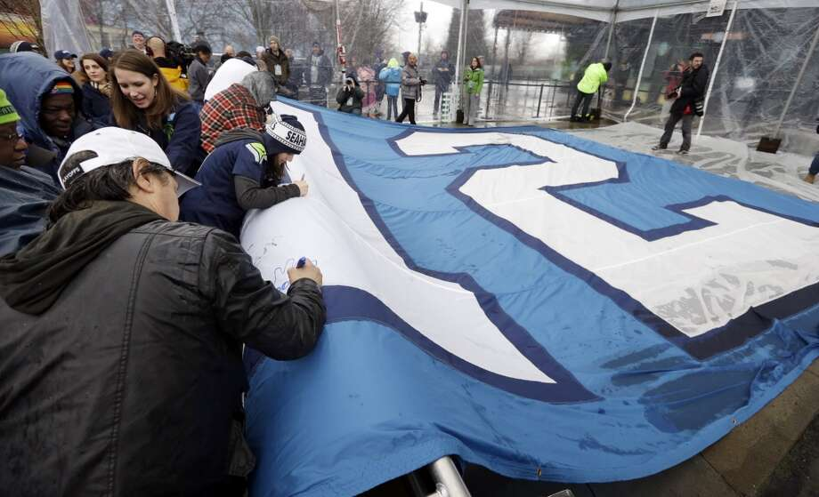 "Seattle Seahawks fans sign a 25-by-35-foot ""12th Man"" flag, which honors fans,  Wednesday, Jan. 29, 2014, near the Space Needle in Seattle. The flag will be sent to the east coast and presented to the team on Sunday, the day that the Seahawks play the Denver Broncos Sunday in Super Bowl XLVIII. (AP Photo/Elaine Thompson) Photo: Elaine Thompson, Associated Press"