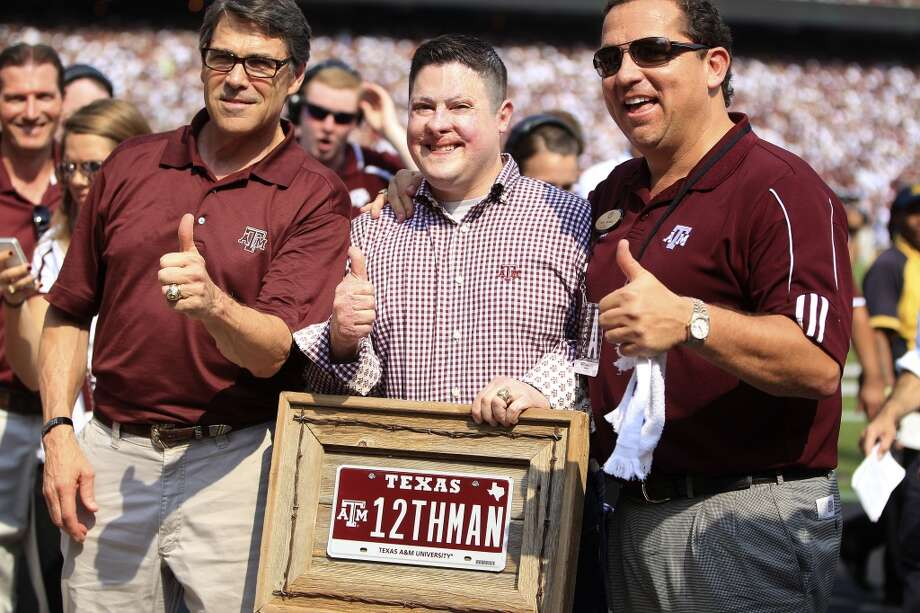 Marine Captain Daniel Moran, Aggie class of 2003 gets his photo taken with Governor Rick Perry, left, after receiving the 12th man âà à special Aggie license plate bought by Houston lawyer Tony Buzbee,right, during a time out in the second quarter of a college football game at Kyle Stadium, Saturday, Sept. 14, 2013, in College Station .  ( Karen Warren / Houston Chronicle ) Photo: Karen Warren, Houston Chronicle