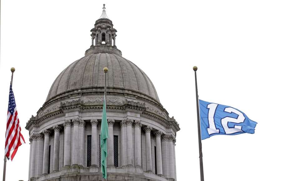 "A Seattle Seahawks' ""12th Man"" flag, symbolizing fan support of the NFL football team, flutters in front of the state Capitol building Tuesday, Jan. 28, 2014, in Olympia, Wash. The Seahawks play the Denver Broncos Sunday in Super Bowl XLVIII in East Rutherford, N.J. (AP Photo/Elaine Thompson) Photo: Elaine Thompson, Associated Press"