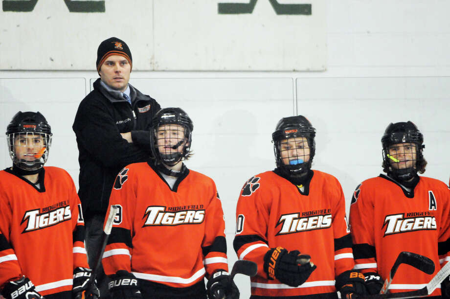 Ridgefield Coach Shaun Gallagher watches game action as Greenwich hosts Ridgefield High School in a boys hockey game at Dorothy Hamill Rink in Greenwich, Conn., Jan. 30, 2014. Photo: Keelin Daly / Stamford Advocate Freelance