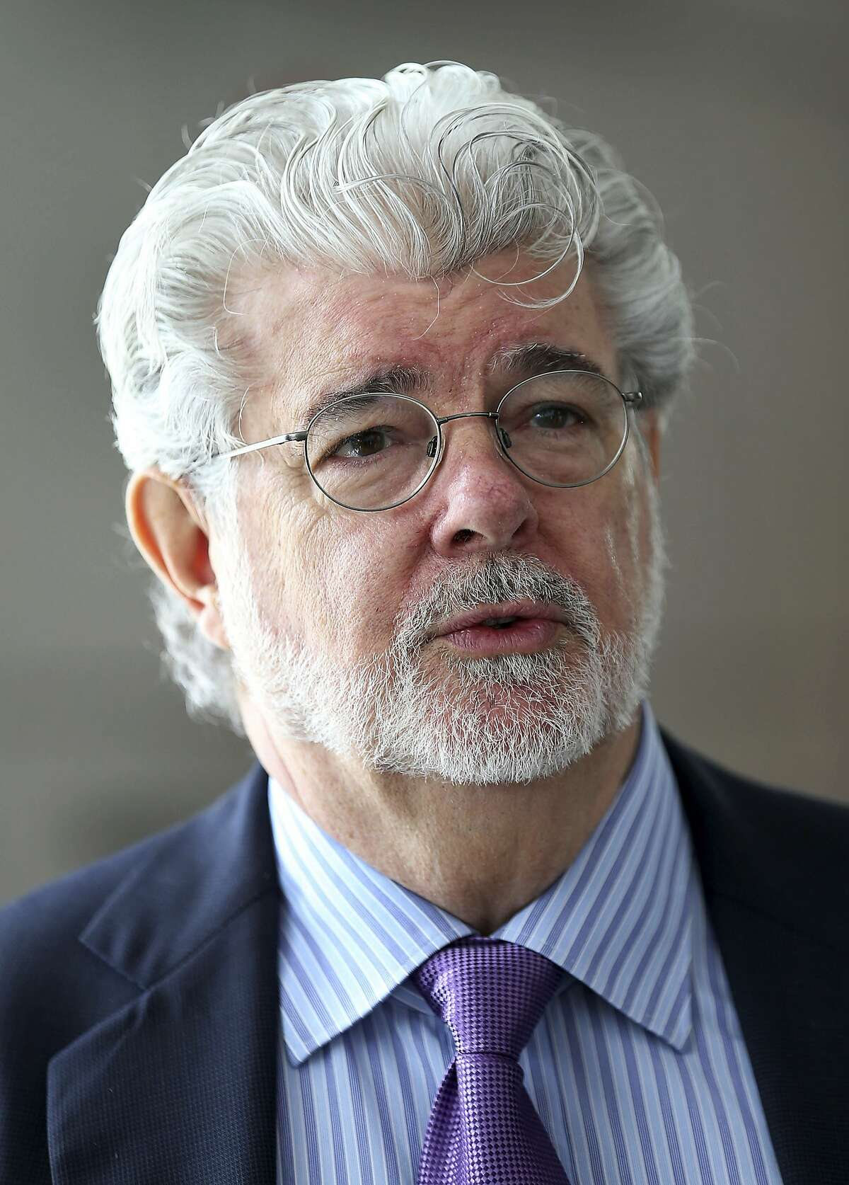 """""""Star Wars"""" creator George Lucas arrives for the opening ceremony of the """"Sandcrawler"""" building, Thursday, Jan. 16, 2014 in Singapore. The """"Sandcrawler"""" building, aptly named due to its resemblance to a large vehicle featured in the original """"Star Wars"""" film, is home to the regional headquarters for Lucasfilm Singapore, The Walt Disney Company (South East Asia) and ESPN Asia Pacific. (AP Photo/Wong Maye-E)"""