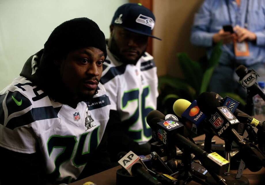 Seattle Seahawks running back Marshawn Lynch, left, answers questions along side teammate Michael Robinson during a media availability Thursday, Jan. 30, 2014, in Jersey City, N.J. The Seahawks and the Denver Broncos are scheduled to play in the Super Bowl XLVIII football game Sunday, Feb. 2, 2014. (AP Photo) ORG XMIT: NJJR102 Photo: Byline Withheld / AP