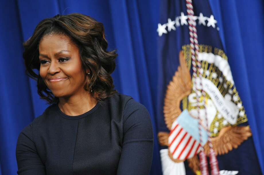 US First Lady Michelle Obama smiles as US President Barack Obama speaks during an event on expanding college opportunity in the South Court Auditorium of the Eisenhower Executive Office Building, next to the White House on January 16, 2014 in Washington, DC. Michelle Obama turns 50 on January 17, 2014 as one of America's most respected women, but despite her popularity she is yet to break the mold as First Lady -- one of the toughest jobs in politics. The former Michelle Robinson did not take to politics quickly in the shadow of her high wattage husband and was even a liability early on in his 2008 campaign. But she has evolved into a polished performer -- and at key moments in the president's reelection bid breathed new life into his political persona, when he seemed weary and uninspired. AFP PHOTO/Mandel NGANMANDEL NGAN/AFP/Getty Images Photo: Mandel Ngan, AFP/Getty Images