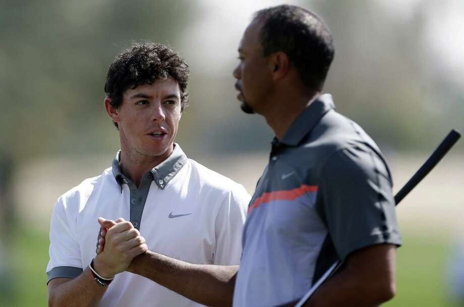 Rory McIlroy (left) and Tiger Woods shake hands during the first round of the Dubai Desert Classic. McIlroy took the lead with a 63, while Woods was five shots behind with a 68. Photo: Karim Sahib / Getty Images / AFP