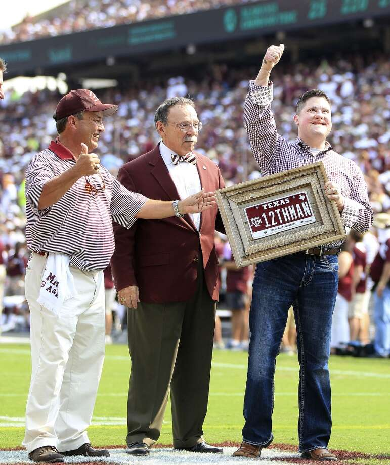 Marine Captain Daniel Moran, Aggie class of 2003 receives the 12th man âÄì special Aggie license plate bought by Houston lawyer Tony Buzbee, during a time out in the second quarter of a college football game at Kyle Stadium, Saturday, Sept. 14, 2013, in College Station .  ( Karen Warren / Houston Chronicle ) Photo: Karen Warren, Houston Chronicle