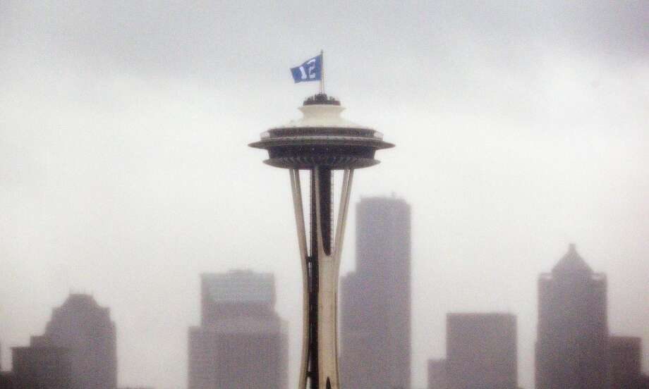 "A ""12th Man"" flag, honoring Seattle Seahawks fans, is barely visible as it flutters atop the Space Needle in the rain Wednesday, Jan. 29, 2014, in Seattle. The Seahawks play the Denver Broncos in Super Bowl XLVIII on Sunday. (AP Photo/Elaine Thompson) Photo: Elaine Thompson, Associated Press"