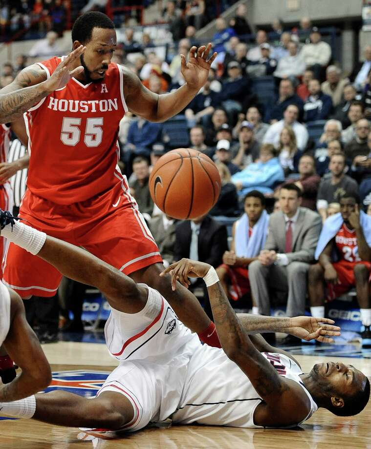 Connecticut's Phillip Nolan, bottom, passes the ball as Houston's J.J. Richardson, left, defends during the first half of an NCAA college basketball game, Thursday, Jan. 30, 2014, in Storrs, Conn. (AP Photo/Jessica Hill) Photo: Jessica Hill, Associated Press / Associated Press