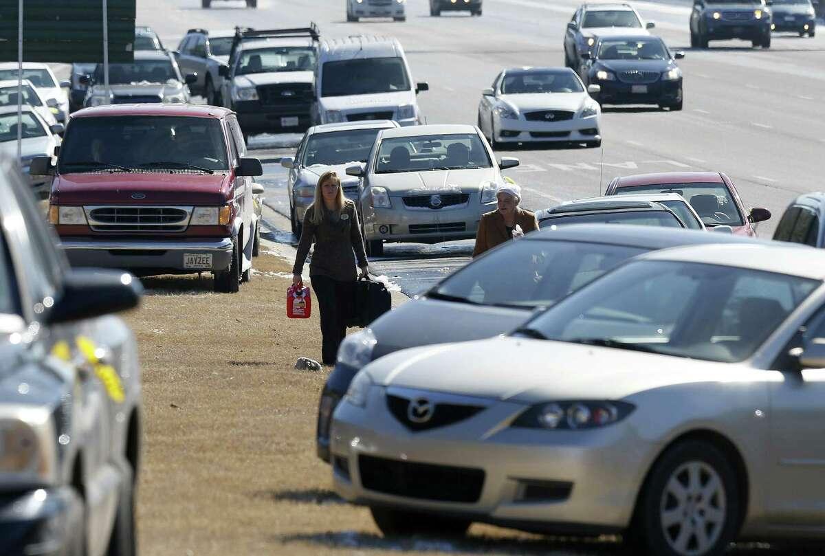 Karen Hurst (left) carries a gas can as she helps Ann Batsun recover her car on Interstate 75 in Atlanta.