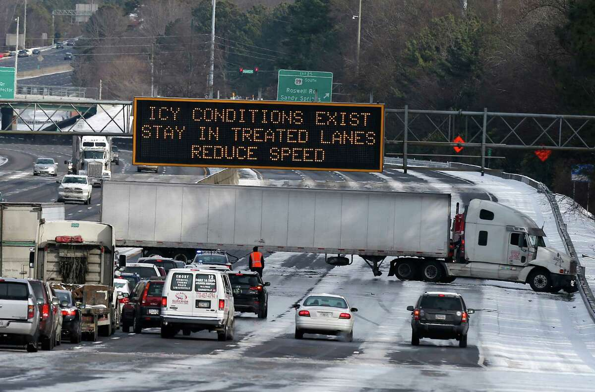 A truck blocks all east-bound lanes of Interstate 285 in Sandy Spring, Ga. after htting an icet patch of road. Wednesday, Jan. 29, 2014, in Atlanta. Some interstates remained clogged by jackknifed 18-wheelers Wednesday afternoon, more than 24 hours after snow began falling on the city. (AP Photo/John Bazemore)