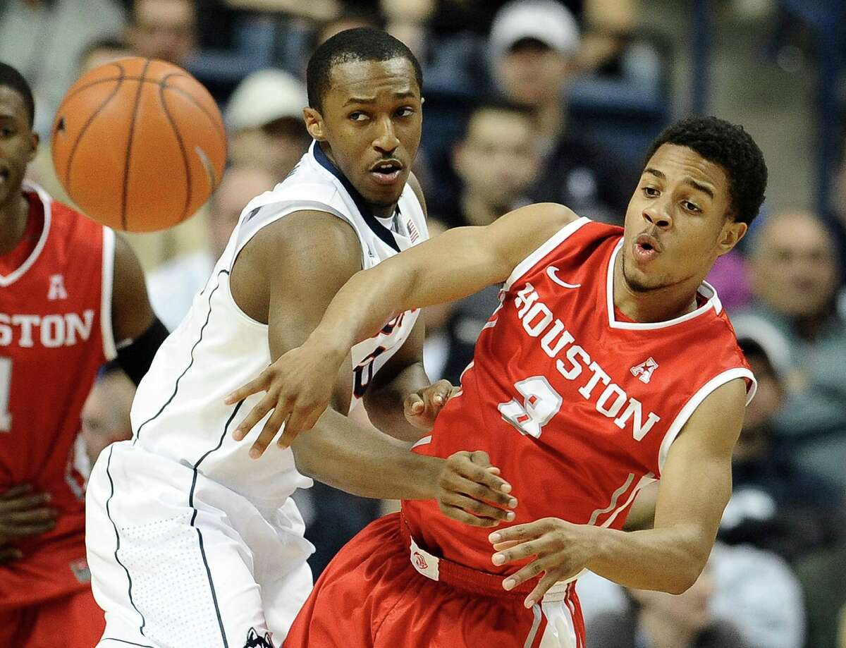 Houston's Jaaron Simmons passes as Connecticut's Lasan Kromah defends during the first half of an NCAA college basketball game, Thursday, Jan. 30, 2014, in Storrs, Conn. (AP Photo/Jessica Hill)