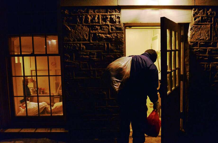A homeless man carrying bags of his belongings walks into the shelter at the First Congregational Church in Danbury on Wednesday, the night of the Connecticut  homeless count. Photo: Tyler Sizemore / The News-Times