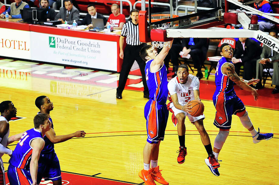 Lamar Cardinals Anthony Holliday, No. 2, center, drives the ball in against Houston Baptist Huskiest at the Montagne Center. Michael Rivera/@michaelrivera88