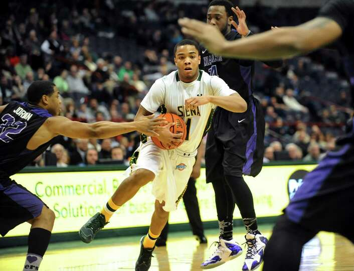 Siena's Marquis Wright, center, controls the ball during their basketball game against Niagara on Th