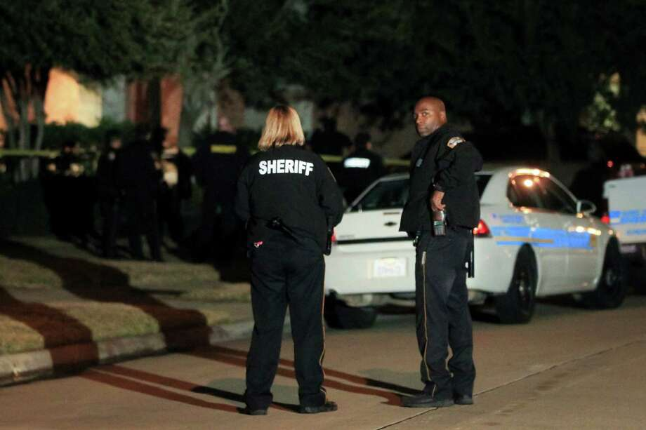 Officers work the scene in the 14000 block of Fosters Creek in northwest Harris County, where sheriff's deputies said  four dead people were found at a home on Thursday. Photo: Karen Warren, Houston Chronicle / © 2014  Houston Chronicle