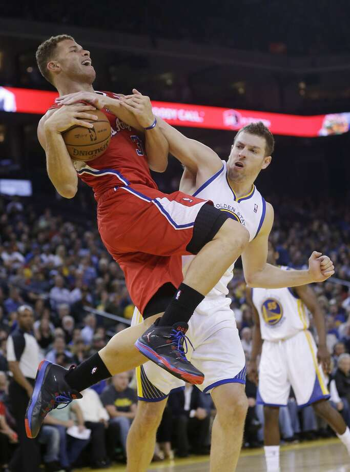 The Clippers' Blake Griffin (left) is fouled by the Warriors' David Lee as he goes up for a shot. Photo: Associated Press