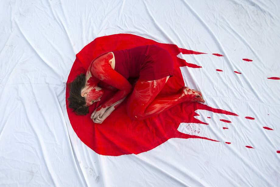 Cold hearts in the Land of Rising Sun: In Tel Aviv, an Israeli member of the Taiji Dolphin Action Group curls up on a sheet 