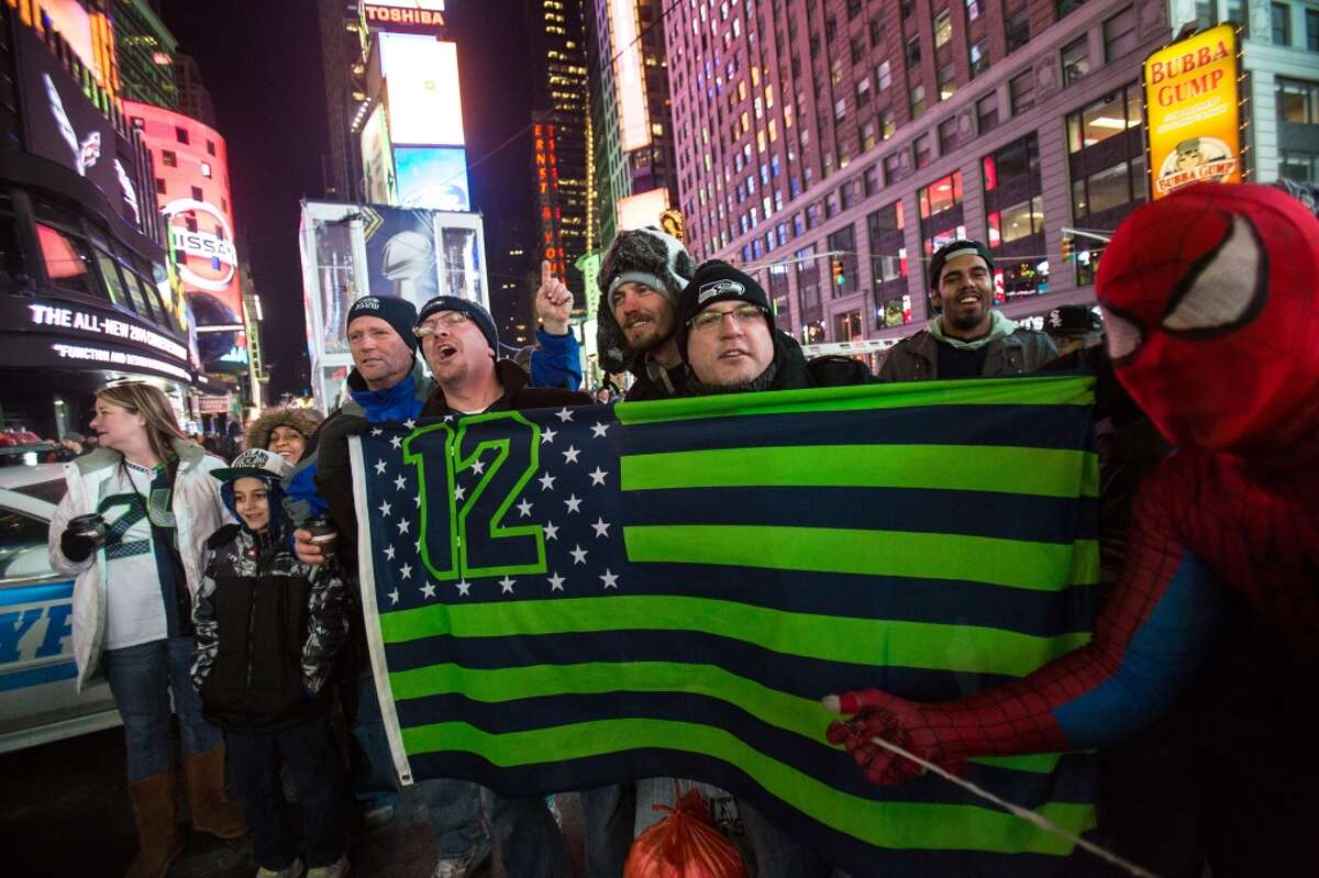 Seahawks fans hold up a flag in Times Square on Thursday, January, 30, 2014 in New York City as hype for the Super Bowl continues to build in The Big Apple. (Joshua Trujillo, seattlepi.com)