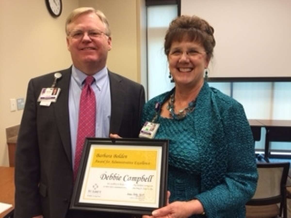 Norman Stephens, CEO of St. Luke's Hospital at The Vintage, presents Debbie Campbell with the Barbara Bolden Award.