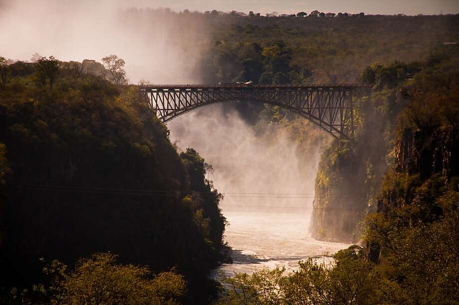 "The name ""Rhodesia"" came from Cecil Rhodes, who pushed British rule north from the South Africa Cape Colony, where he was prime minister. The British South Africa Company administered Northern and Southern Rhodesia from 1891 until the United Kingdom took it over in 1923. Rhodes also was behind this 650-foot-long iron bridge across Victoria Falls, the world's largest waterfall, which separated Northern and Southern Rhodesia. Photo: Mark Sissons, Special To The Chronicle"