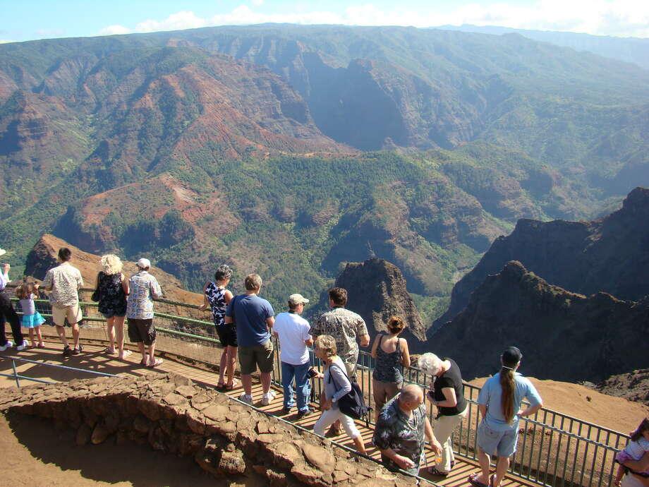 This Jan. 5, 2012 photo shows tourists lining up to view Waimea Canyon on the island of Kauai, Hawaii. The natural wonder has been dubbed the Grand Canyon of the Pacific. Photo: Joe Kafka, AP / AP