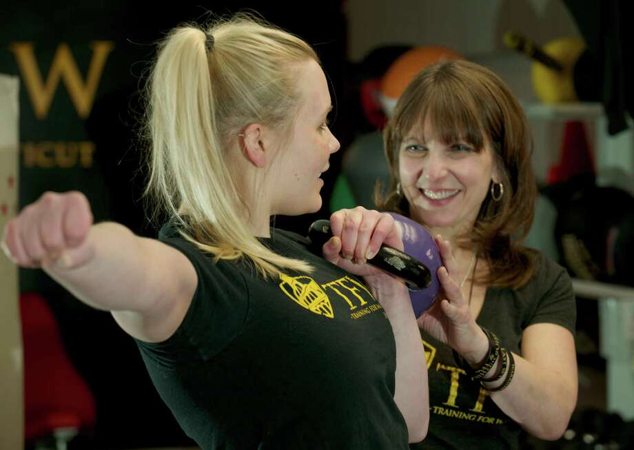 Elizabeth Billings, 25, of Danbury, gets instruction from fitness coach Debra Rydziel, at Andreas Washeim's Bethel, Conn, fitness studio, Training for Warriors on Thursday, January 30, 2014. Photo: H John Voorhees III / The News-Times Freelance