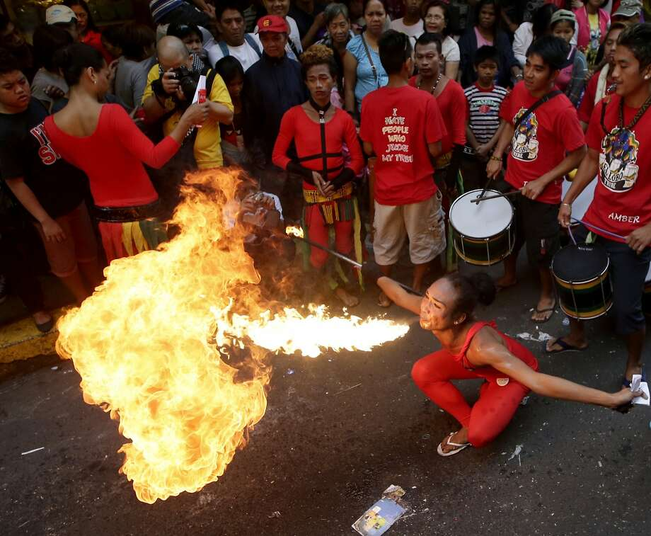 A fire eater performs in front of a business establishment in celebration of Chinese New Year at Manila's Chinatown district of Binondo, Philippines, Friday, Jan. 31, 2014. This year in the Chinese Lunar calendar is the Year of the Horse. Photo: Bullit Marquez, Associated Press