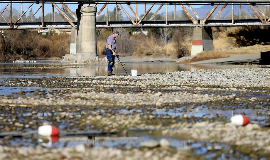 In this file photo, Hugh Beggs of Santa Rosa searches for coins in the middle of the Russian River in Healdsburg, taking advantage of the way below normal river flow. Seventeen rural communities in drought-stricken California are in danger of running out of water within four months, according to a list compiled by state officials. Wells are running dry or reservoirs are nearly empty in some communities. Photo: Kent Porter, Associated Press